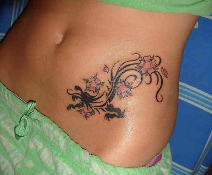 Smok i kwiaty tatuaż brzuch