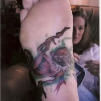 Brązowy trol tatuaż na stopie