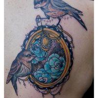 Dwa ptaki i ramka z kwiatami tatuaż