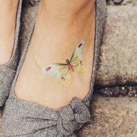 Jasny motyl tatuaż na stopie