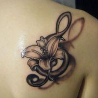 Klucz wiolinowy i lilia tatuaż