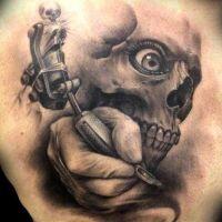 Ręka z maszynką do tatuaży i czaszka
